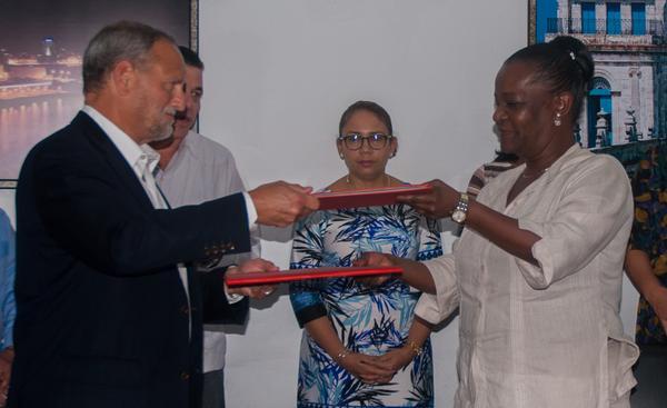 Scott Gilbert (I), Director de COABANA TRADING LLC, e Isabel O´Reilly (D), Directora de CUBAEXPORT, intercambian contratos firmados de compraventa internacional para la exportación de carbón vegetal artesanal de marabú, en la sede del Ministerio del Comercio Exterior y la Inversión Extranjera (MINCEX), en La Habana, el 5 de enero de 2017. ACN FOTO/ Diana Inés RODRÍGUEZ RODRÍGUEZ