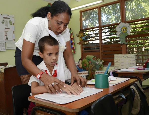 Alumnos ciego, del aula multigrado de tercero y cuarto de la escuela especial José Martí, lee gracias al sistema Braille, con la ayuda de su maestra, durante una sesión habitual de clases, en la provincia Pinar del Río, Cuba, el 17 de octubre de 2017. ACN FOTO/Rafael FERNÁNDEZ ROSELL