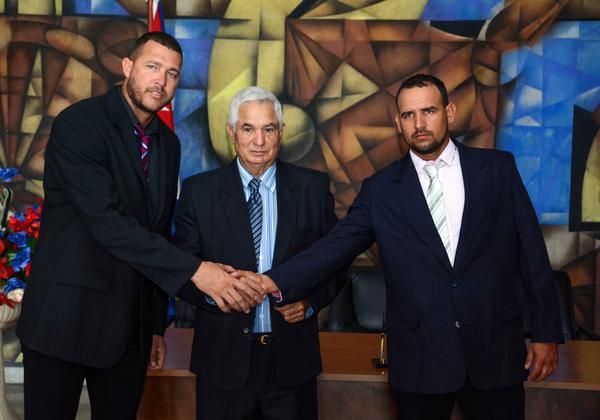 Lázaro Blanco (I), lanzador del equipo Granma, Higinio Vélez (C), presidente de la federación cubana de béisbol, y Yordan Maduley (D), torpedero del equipo Holguín, durante la firma del contrato con el equipo Capitales de Québec de la liga Can-Am, en la Ciudad Deportiva de La Habana, el 25 de abril de 2018. ACN FOTO/ Abel PADRÓN PADILLA/