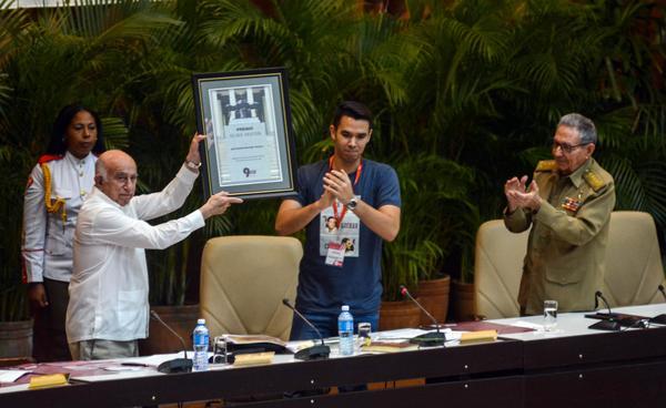 José Ramón Machado Ventura (I), Segundo Secretario del Comité Central del Partido Comunista de Cuba (CC PCC), recibe el Premio Alma Mater de manos de Raúl Alejandro Palmero Fernández (C), presidente ratificado de la Federación Estudiantil Universitaria (FEU), en presencia del General de Ejército Raúl Castro Ruz (D), Primer Secretario del CC PCC, durante la Sesión Plenaria del IX Congreso de la FEU, en el Palacio de Convenciones de La Habana, el 8 de julio de 2018. ACN FOTO/ Abel PADRÓN PADILLA