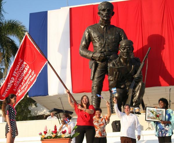 Belkis Díaz Jiménez (C), secretaria general de la Federación de Mujeres Cubanas (FMC) en Sancti Spíritus, porta la bandera que acredita a la provincia como Vanguardia Nacional en la emulación por el 8 de Marzo, estandarte entregado durante la conmemoración nacional por el Día Internacional de la Mujer, que tuvo por sede la plaza Mayor General Serafín Sánchez Valdivia, en la ciudad de Sancti Spíritus, el 8 de marzo de 2018. ACN FOTO/Oscar ALFONSO SOSA