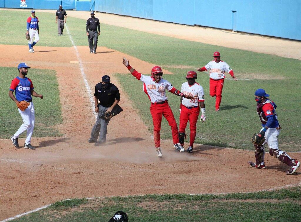 Béisbol: Yoisnel Camejo (centro, uniforma rojo y blanco, saltando) anotó por wild pitch la carrera que le dió la victoria a Matanzas sobre Granma en el quinto juego de la final beisbolera cubana que se desarrolla en el estadio José Antonio Huelga, en Sancti Spíritus, Cuba, el 2 de abril de 2021. ACN FOTO/Oscar ALFONSO SOSA